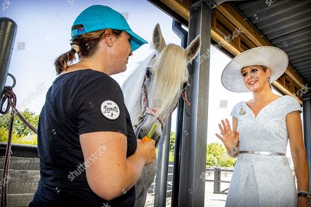 Queen Maxima of the Netherlands (R) looks at a horse as she attends the opening of riding school No Limits Noordwijk, in Noordwijkerhout, The Netherlands, 25 June 2019. The small-scale riding school provides therapeutic riding lessons for people with anxiety, autism, ADHD or Down's syndrome.