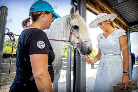 Queen Maxima of the Netherlands (R) feeds a horse as she attends the opening of riding school No Limits Noordwijk, in Noordwijkerhout, The Netherlands, 25 June 2019. The small-scale riding school provides therapeutic riding lessons for people with anxiety, autism, ADHD or Down's syndrome.