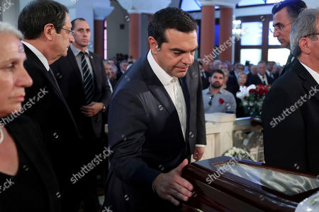 Greece's Prime minister Alexis Tsipras touches the coffin of the former Cyprus' President Dimitris Christofias during his state funeral at the Orthodox Christian Church of the Lord's Wisdom in capital Nicosia, Cyprus, . European communist and left-wing party heads and leaders from ethnically split Cyprus' breakaway Turkish Cypriot community were among those attending a funeral service for the country's former president Christofias