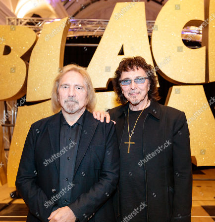 Stock Picture of Geezer Butler and Tony Iommi pose in front of a giant Black Sabbath logo