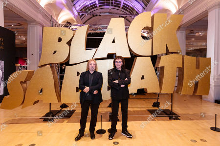 Geezer Butler and Tony Iommi pose in front of a giant Black Sabbath logo