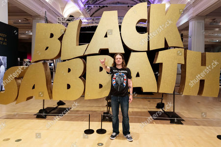 Stock Photo of Superfan Chris Hopkins poses in front of the Black Sabbath logo