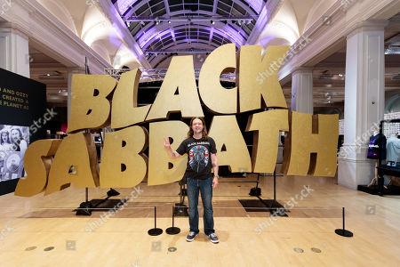 Superfan Chris Hopkins poses in front of the Black Sabbath logo