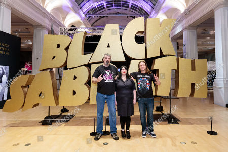 Superfan Ric Lovett, Home of Metal organiser Lisa Meyer, and superfan Chris Hopkins pose in front of a giant Black Sabbath logo