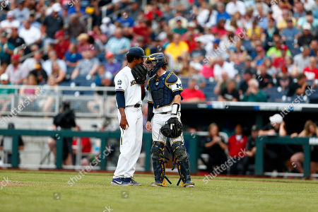Michigan pitcher Isaiah Paige, left, talks to catcher Joe Donovan in the third inning of Game 2 against Vanderbilt in the NCAA College World Series baseball finals in Omaha, Neb