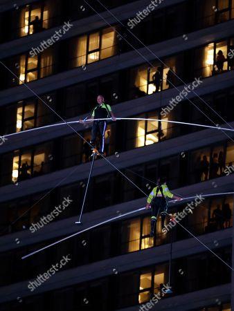 Nik Wallenda, Lijana Wallenda. Aerialists Nik Wallenda, top, steps over his sister, Lijana, bottom, as they walk on a high wire above Times Square, in New York