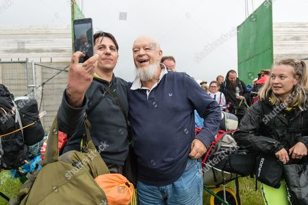 Michael Eavis poses for a selfy with a festival goers shortly after opening the gates of the festival for the first time, after giving a short speech to those at the front of the queue