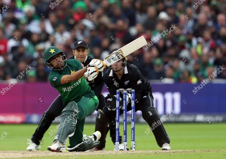 Pakistan's batsman Babar Azam, front, watches his shot as New Zealand's wicketkeeper Tom Latham, right, with teammate Ross Taylor looks on during the Cricket World Cup match between New Zealand and Pakistan at the Edgbaston Stadium in Birmingham, England
