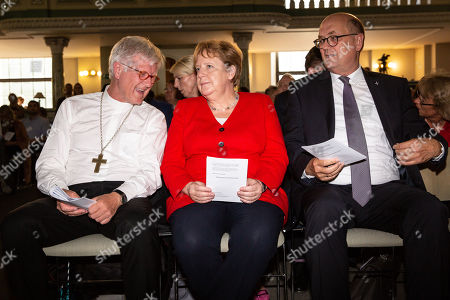 Stock Picture of (L-R) Regional Bishop and Council Chairman of the Evangelical Church in Germany (EKD) Heinrich Bedford-Strohm, German Chancellor Angela Merkel, Plenipotentiary of the Council of the EKD Prelate Martin Dutzmann, Attend the traditional Johannisempfang event at the French Friedrichstadtkirche Church in Berlin, Germany, 26 June, 2019. Politicians, culture figures and other guests gathered in the event organized by the Evangelical Church in Germany (EKD).