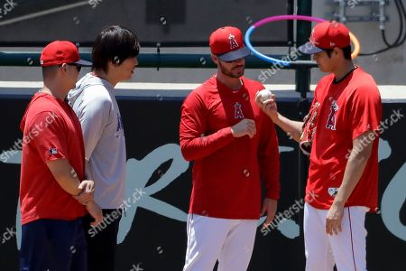 Los Angeles Angels' Shohei Ohtani, right, talks with pitching coach Doug White after throwing in the bullpen before a baseball game against the Cincinnati Reds in Anaheim, Calif., . Ohtani threw off a mound for the first time since Tommy John surgery Oct 1, 2018