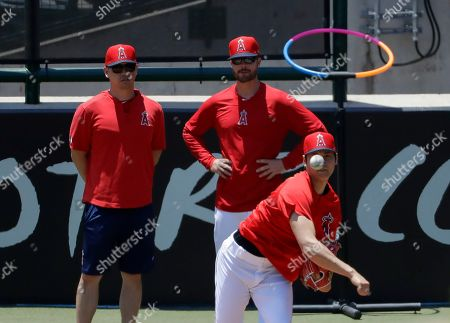 Los Angeles Angels' Shohei Ohtani, right, throws as pitching coach Doug White on in the bullpen before a baseball game against the Cincinnati Reds in Anaheim, Calif., . Ohtani threw off a mound for the first time since Tommy John surgery Oct 1, 2018