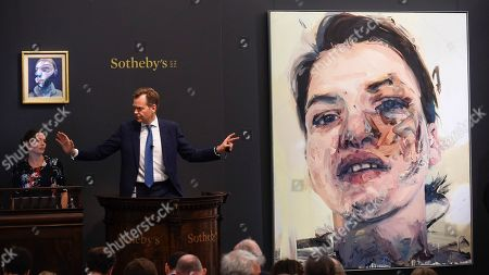 Oliver Barker, Chairman, Sotheby's Europe, fields bids for L Self-Portrait by Francis Bacon, Est. £15,000,000 - 20,000,000 which sold for a hammer price of £14,350,000 and R Shadow Head by Jenny Saville, Est. £3,000,000 - 5,000,000 which sold for a hammer price of £3,500,000