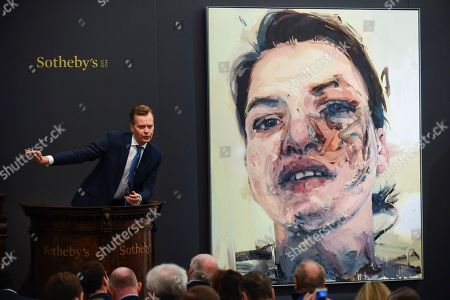 Stock Photo of Oliver Barker, Chairman, Sotheby's Europe, fields bids for Shadow Head by Jenny Saville, Est. £3,000,000 - 5,000,000 which sold for a hammer price of £3,500,000