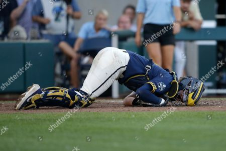 Stock Image of Michigan catcher Joe Donovan (0) falls after being hit by a pitch during the third inning against Vanderbilt in Game 3 of the NCAA College World Series baseball finals in Omaha, Neb