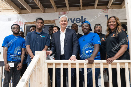 Detroit, MI: JPMorgan Chase Chairman and CEO Jamie Dimon, center, stands with students and recent graduates from A. Philip Randolph Technical High School along with principal Krista McKinney-King, right, on the porch of a house built in one of the school's classrooms as part of the commemoration of JPMorgan Chase's $200 million investment in Detroit on in Detroit