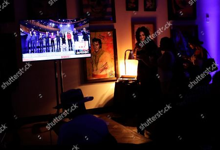 People watch a Democratic presidential debate during a watch party hosted by the former Florida Democratic gubernatorial candidate Andrew Gillum, in Miami