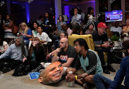 People hold a cutout head of Democratic presidential candidate Sen. Cory Booker, D-N.J., as they watch a Democratic presidential debate during a watch party hosted by the former Florida Democratic gubernatorial candidate Andrew Gillum, in Miami