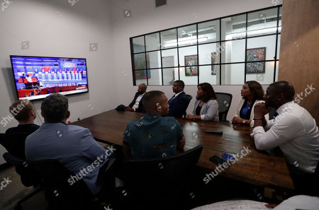 Stock Photo of Former Florida Democratic gubernatorial candidate Andrew Gillum, right, watches the Democratic presidential debate during a watch party, in Miami