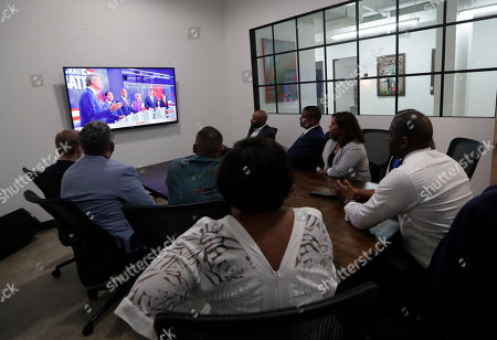 Stock Picture of Former Florida Democratic gubernatorial candidate Andrew Gillum, right, watches the Democratic presidential debate during a watch party, in Miami