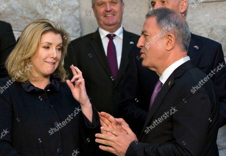 British Defense Minister Penny Mordaunt, left, speaks with Turkish Defense Minister Hulusi Akar, right, at the beginning of a group photo of NATO defense ministers at NATO headquarters in Brussels