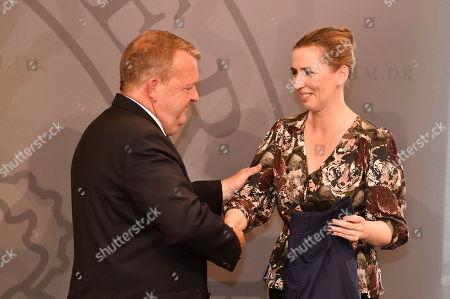 Stock Photo of Former Danish Prime Minister Lars Lokke Rasmussen (L) presents a gift, a pair of work trousers, to newly assigned Danish Prime Minister Mette Frederiksen (R) in Copenhagen, Denmark, 27 June 2019.