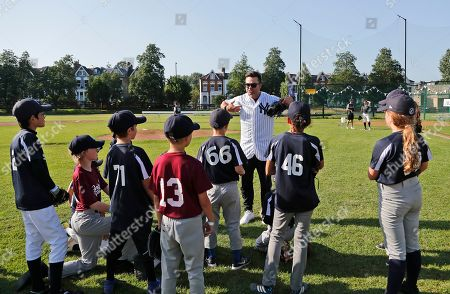 Yankees' Nick Swisher, centre, teaches young fans during a private Baseball Clinic in London, . The Yankees are hosting for approximately 100 youth in the London community in conjunction with the London Meteorites Baseball and Softball Club this private Baseball Clinic