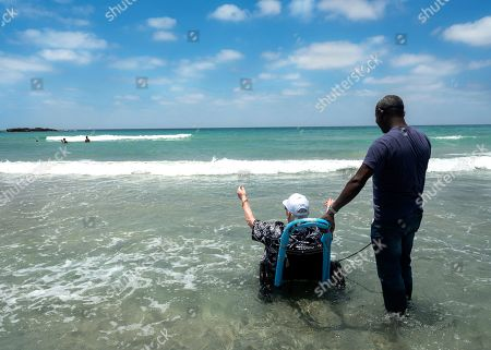 Segal (R), a care giver for Holocaust survivors helps Judith, a holocaust survivor in her eighties, enjoy the Mediterranean Sea during a visit of some 50 survivors to the beach at Kibbutz Ma'agan Micha'el, south of Haifa, Israel, 27 June 2019. Judith was a child in Hungary when the Nazis invaded in World War II. She lost all her family but managed to survive and at the close of the war had only the clothes on her back. She always had wanted to see the sea and today was the first time she was able to splash in the salt water.