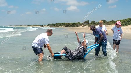 Eliran Keren (L), the son of a Holocaust survivor and Segal (R), another carer of Holocaust survivors help bring Judith, a holocaust survivor in her eighties, into the Mediterranean Sea during a visit of some 50 survivors to the beach at Kibbutz Ma'agan Micha'el, south of Haifa, Israel, 27 June 2019. Judith was a child in Hungary when the Nazis invaded in World War II. She lost all her family but managed to survive and at the close of the war had only the clothes on her back. She always had wanted to see the sea and today was the first time she was able to splash in the salt water.