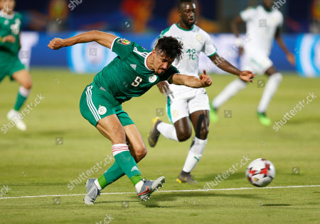 Algeria's Baghdad Bounedjah shoots in front of Senegal's Youssouf Sabaly during the African Cup of Nations group C soccer match between Algeria and Senegal at 30 June Stadium in Cairo, Egypt