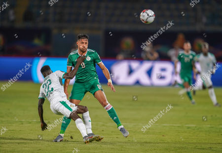 Moussa Wague of Senegal and Baghdad Bounedjah of Algeria challenging for the ball during the African Cup of Nations match between Senegal and Algeria at the 30 June Stadium in Cairo, Egypt
