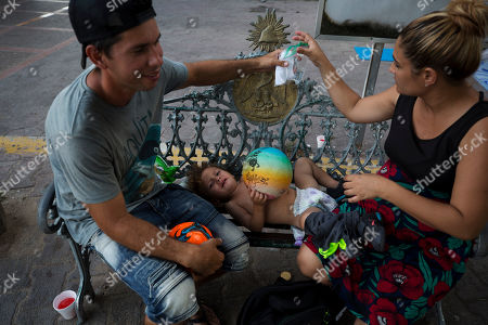 Cuban migrants Viviana Martinez, right, and her husband Sergio Rodriguez, 35, change the diaper of their son Sergio Jr., 18 months, on a bench at the entrance to the Puerta Mexico international bridge, in Matamoros, Tamaulipas state, Mexico, . Martinez, who estimates she is at least five months pregnant, says she has not been able to see a doctor for a single pre-natal visit since becoming pregnant. Hundreds of migrants from Central America, South America, the Caribbean and Africa have been waiting for their number to be called at the bridge in downtown Matamoros, to have the opportunity to request asylum in the U.S