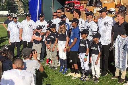 Stock Picture of Former New York Yankees baseball players, from left wearing white jerseys, are Reggie Jackson, Carlos Beltran, Mariano Rivera, Alex Rodriguez, Andy Pettitte, Hideki Matsui, Nick Swisher and Aaron Boone, along with Yankees principal owner Hal Steinbrenner, right, pose with young players after presenting baseball equipment to the London Mets youth baseball club at Finchley Park in London