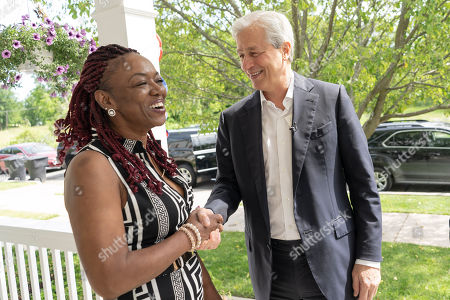 CO.- Detroit, MI: Detroit resident Trina Patterson, left, shakes hands with JPMorgan Chase Chairman and CEO Jamie DImon on the front porch of her residence on for the commemoration of JPMorgan Chase's $200 million investment in Detroit