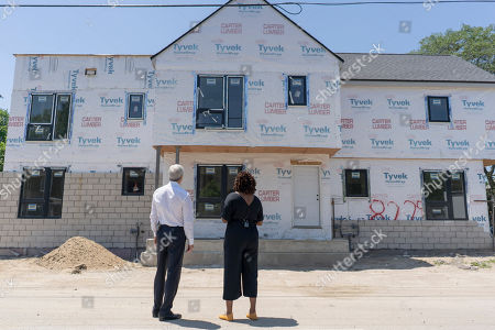CO.- Detroit, MI: Develop Detroit CEO Sonya Mays, right, shows JPMorgan Chase Chairman and CEO Jamie Dimon, left, one of many buildings undergoing renovation in the North End neighborhood of Detroit on for the commemoration of JPMorgan Chase's $200 million investment in Detroit