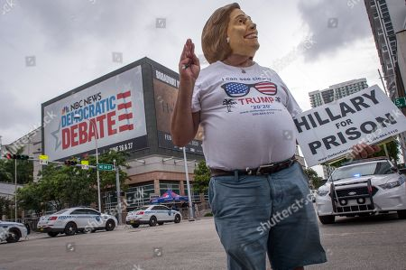 Stock Image of A supporter of US President Donald J. Trump disguises himself with a mask of Hillary Clinton, outside of Adrienne Arsht Center of the Performing Arts, where the second night of the first Democratic Presidential Debate will be held in Miami, Florida, USA, 27 June 2019. The second night of the first democratic presidential debate will be between Former Vice President Joe Biden, Senator Bernie Sanders of Vermont, Mayor Pete Buttigieg of South Bend, Indiana, Senator Kamala Harris of California, Senator Kristen Gillibrand of New York, Representative Eric Swalwell of California, Former Governor of Colorado John Hickenlooper, Senator Michael Bennet of Colorado, Author Marianne Williamson, and Businessman Andrew Yang.