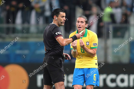 Brazil's Filipe Luis, right, protests after referee Roberto Tobar showing a yellow card during a Copa America quarterfinal soccer match against Paraguay at the Arena do Gremio in Porto Alegre, Brazil