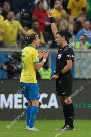 Referee Roberto Tobar shows the yellow card to Brazil's Filipe Luis during a Copa America quarterfinal soccer match against Paraguay at the Arena do Gremio in Porto Alegre, Brazil
