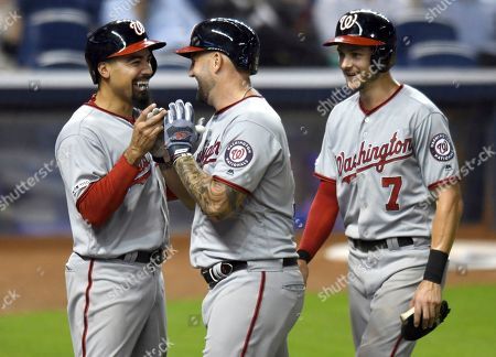 Washington Nationals' Matt Adams, center, celebrates a three-run home run against the Miami Marlins in the sixth inning of a baseball game with teammates Anthony Rendon, left, and Trea Turner (7), in Miami