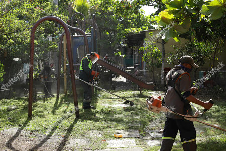 Municipal workers mow the lawn near a derelict swing set that is part of the Alta Vista neighborhood where migrant Oscar Martinez Ramirez and his two-year-old daughter Valeria lived, San Martin, El Salvador, . Martinez Ramirez and his daughter drowned this week in each other's arms while trying to cross the Rio Grande into Texas