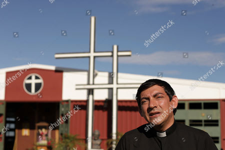 Father Manuel Lozano talks during an interview in front of his church in the Alta Vista neighborhood in San Martin, El Salvador, . Lozano estimates that a third his parishioners have left the country since 2015, risking the dangerous trek north toward the United States
