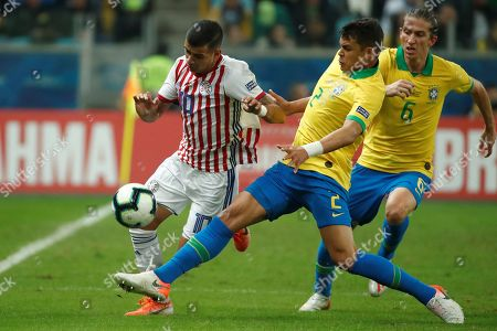 Brazilians Thiago da Silva (C) and Filipe Luis (R) vie for the ball with Paraguayan Derlis Gonzalez (L) during the Copa America 2019 quarter-finals soccer match between Brazil and Paraguay at Arena do Gremio Stadium in Porto Alegre, Brazil, 27 June 2019.