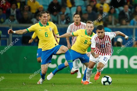 Paraguayan Derlis Gonzalez (R) escapes with the ball from Brazilians Filipe Luis (L) and Arthur (C) during the Copa America 2019 quarter-finals soccer match between Brazil and Paraguay at Arena do Gremio Stadium in Porto Alegre, Brazil, 27 June 2019.