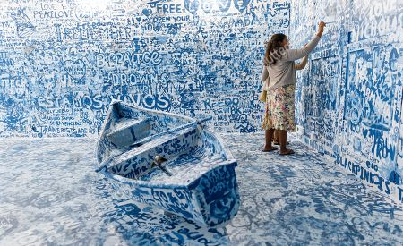 People visit the interactive installation 'Add Color (Refugee Boat)' by artist Yoko Ono, made up of an empty room with a boat where visitors can paint messages and images on walls, in New York, New York, USA, 27 June 2019. The exhibit is part of the Lower Manhattan Cultural Council's annual River to River Festival which runs until 29 June 2019.