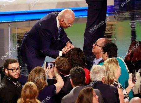 Democratic presidential candidate former Vice-President Joe Biden grabs the hand of Fred Guttenberg, who lost a daughter in the Parkland shooting, following the Democratic primary debate hosted by NBC News at the Adrienne Arsht Center for the Performing Arts, in Miami