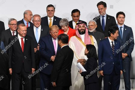 US President Donald J. Trump (C-L) greets Chinese President Xi Jingping (bottom, C) as other world leaders pose for a family photo on the first day of the G20 summit in Osaka, Japan, 28 June 2019. It is the first time Japan hosts a G20 summit. The summit gathers leaders from 19 countries and the European Union to discuss topics such as global economy, trade and investment, innovation and employment.
