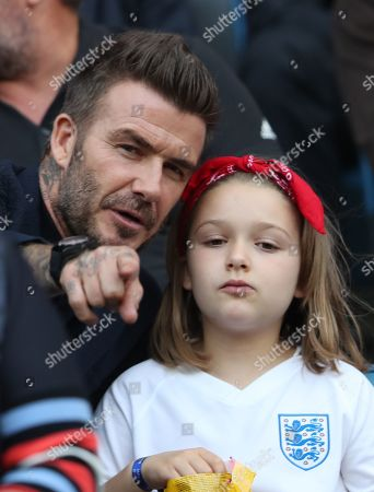 David Beckham and his daughter Harper Beckham watch from the stands.