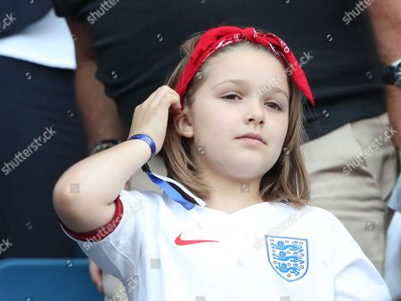 Harper Beckham  wearing England football Shirt watches from the stands.