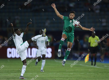 Senegal's Moussa Wague, left, and Algeria's Mohamed Belaili fight for the ball during the African Cup of Nations group C soccer match between Algeria and Senegal at 30 June Stadium in Cairo, Egypt