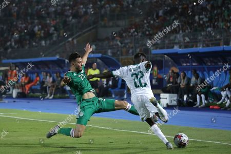Senegal's Moussa Wague, right, plays the ball as Algeria's Amir Bensebaini tries to blocks the ball during the African Cup of Nations group C soccer match between Algeria and Senegal at 30 June Stadium in Cairo, Egypt