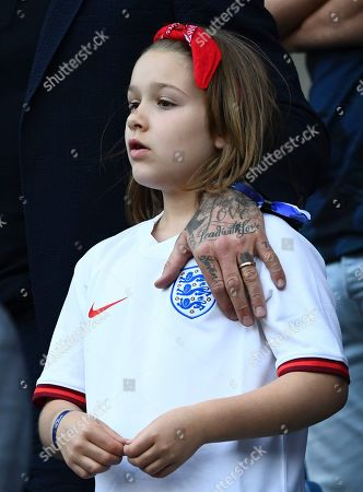 Stock Image of Harper Beckham with David's tattooed hand next to the England badge